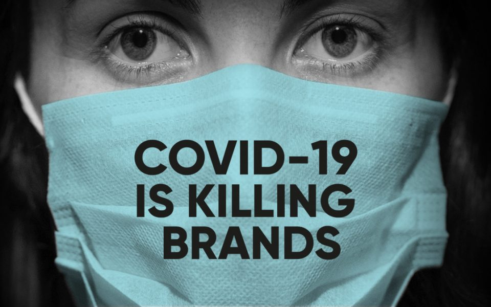 A woman wearing a mask that reads COVID-19 is killing brands